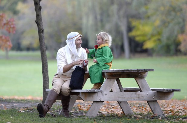 Prime Minister Justin Trudeau, dressed as the Pilot from The Little Prince, left, and his son Hadrien, dressed as the Little Prince, have a treat after trick-or-treating at Rideau Hall, on Halloween, Monday, Oct. 31, 2016 in Ottawa. THE CANADIAN PRESS/Justin Tang